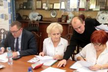 Radny Krzysztof Kroczak sięga po listę obecności.